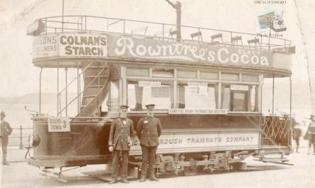 Two men stood in front of a local tram operated by the Scarborough Tramways Company, on the side there is an advertisement for Rowntrees Cocoa